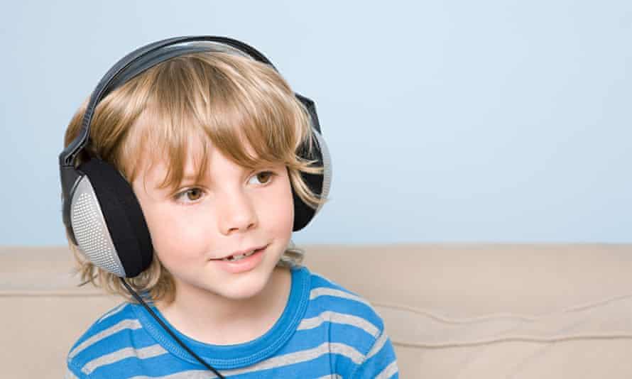 A boy listens to music through headphones