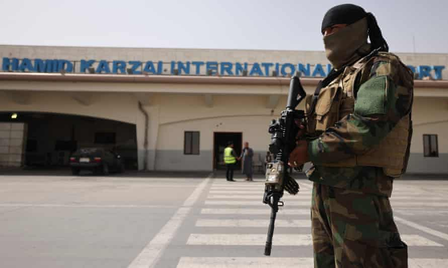 A Taliban fighter stands guard on the tarmac at the airport in Kabul.