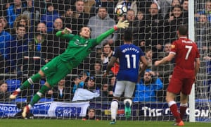 Liverpool's Loris Karius makes a save as his team-mate James Milner and Everton's Theo Walcott look on