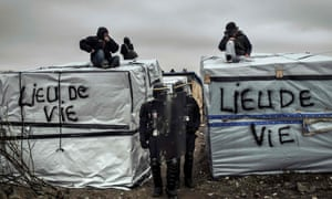 "Policemen stand next to migrants on shelter roofs  in the ""Jungle"" migrant camp, Calais"
