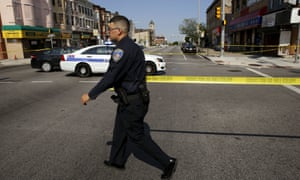 Baltimore police officer attempts to secure a crime scene with tape at the scene of a shooting in West Baltimore.