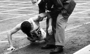 Black and white photo.  A runner in white singlet is being helped up from the ground by an official.