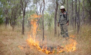 Traditional owner Philip Yam observes a fire he has just lit with a match to create a fire break in savannah woodland at Oriners station in Cape York, Queensland.