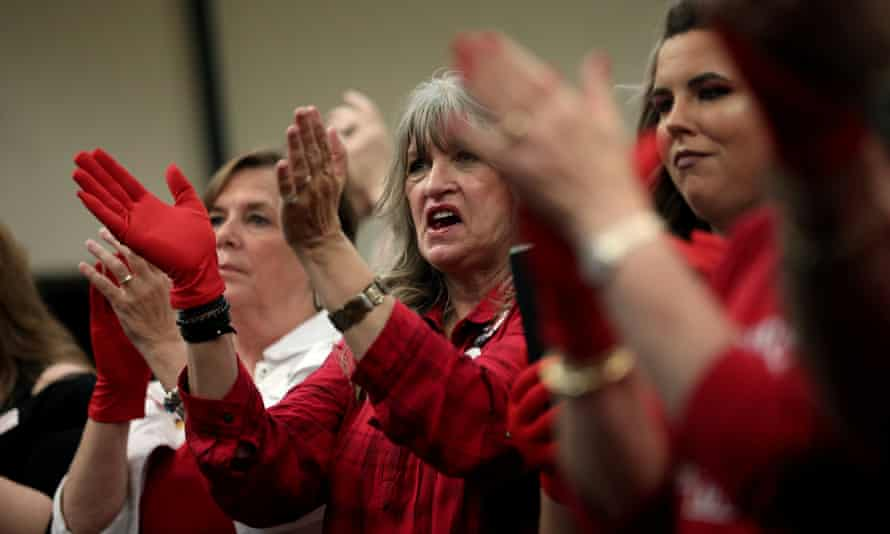 Supporters of Senator Ted Cruz applaud wearing 'Red Wave' gloves at a campaign rally in Victoria, Texas, on 3 November.