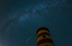 <strong>Pilsum, Germany</strong> A falling star crosses the night sky behind a lighthouse