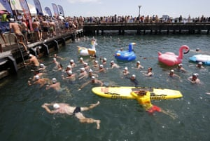 Participants exit the water after the Australia Day Newcastle Harbour Swim.