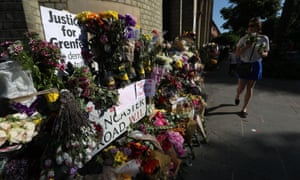People walk past floral tributes outside Notting Hill Methodist church, near Grenfell Tower in west London.