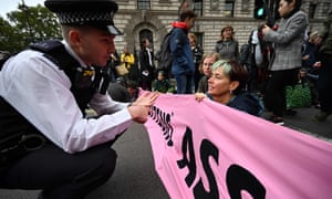 Police officer talks to climate change activists as they block the junction of Whitehall and Parliament Square.