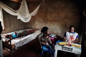 A health coordinator treats patient at a health post in Ekang village