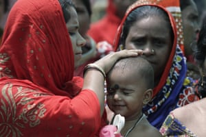 A woman wets the head of a child in Mathurapur, India