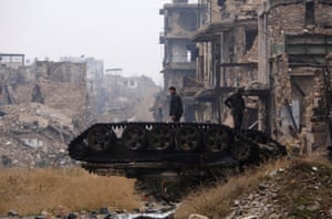 Forces loyal to Syria's president, Bashar al-Assad, stand on top of a damaged tank near the Umayyad mosque