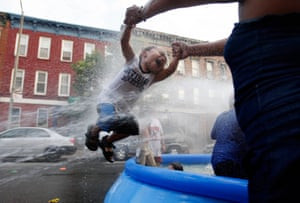 A woman swings a child through a jet of water gushing from a fire hydrant as people in Brooklyn, New York, search for respite from 40C temperatures.