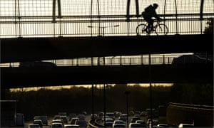 A cyclist crosses the M60 orbital motorway in Manchester.