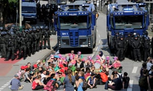 Protesters sit in front of police water cannon vehicles during the G20 summit in Hamburg.