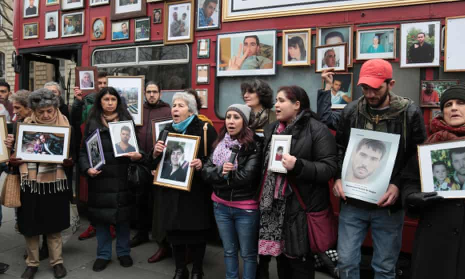 Activists hold portraits of those detained or missing in front of Families for Freedom's red London bus.