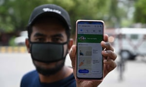 A youth shows the coronavirus contact tracing app Arogya Setu App to a policeman on his mobile as police request commuters to install app during a nationwide lockdown imposed as a preventive measure against the spread of the COVID-19 coronavirus in Allahabad, India on April, Tuesday 21, 2020.