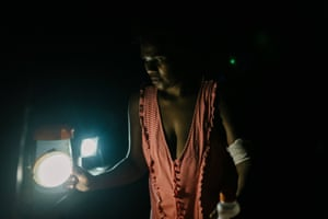 Kwevrie*, 35, makes dinner for her five children with the aid of a solar light, in the open kitchen of an evacuation centre in Lone, West Ambae.  *name changed