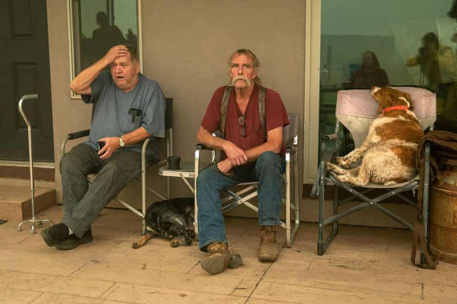 Gould Fickardt, 71, left, and Woody Hovland, 70, of Greenville, sit with their dogs, Primer, right, and Sheva, left, outside a home where they are staying after losing their own homes to the Dixie fire.