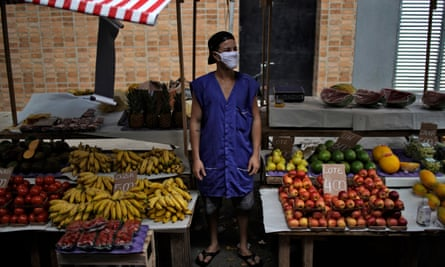 A fruit and vegetable seller waits for customers after street markets were reopened in Rio de Janeiro, Brazil, on 29 April 2020.