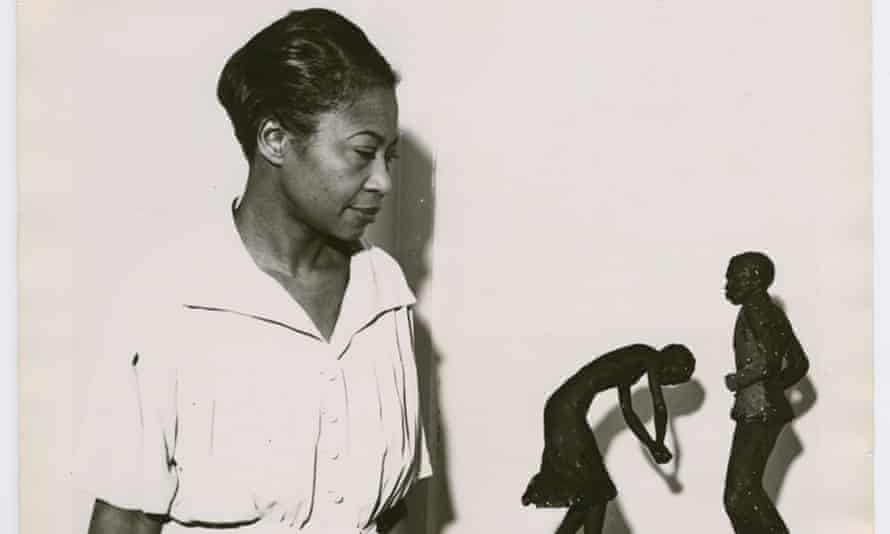 Augusta Savage viewing two of her sculptures, Susie Q and Truckin, 1939