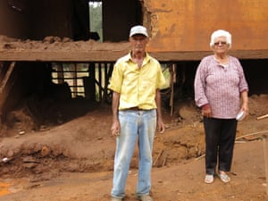 Geraldo Nascimento and Francisca da Silva stand in front of their ruined house.