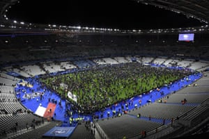 Spectators gather on the pitch of the Stade de France stadium following the match as new of the attacks emerges.