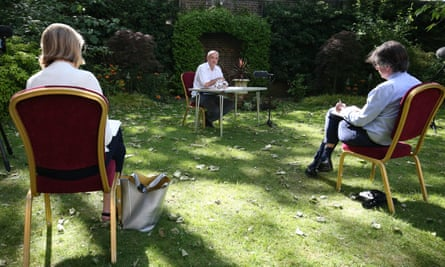 Dominic Cummings, seated at a table in the rose garden of !0 Downing Street, distances himself from journalists sitting on chairs