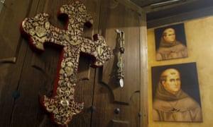 An ornate crucifix hangs on a door near portraits of Junípero Serra at the Carmel Mission in Carmel, California.