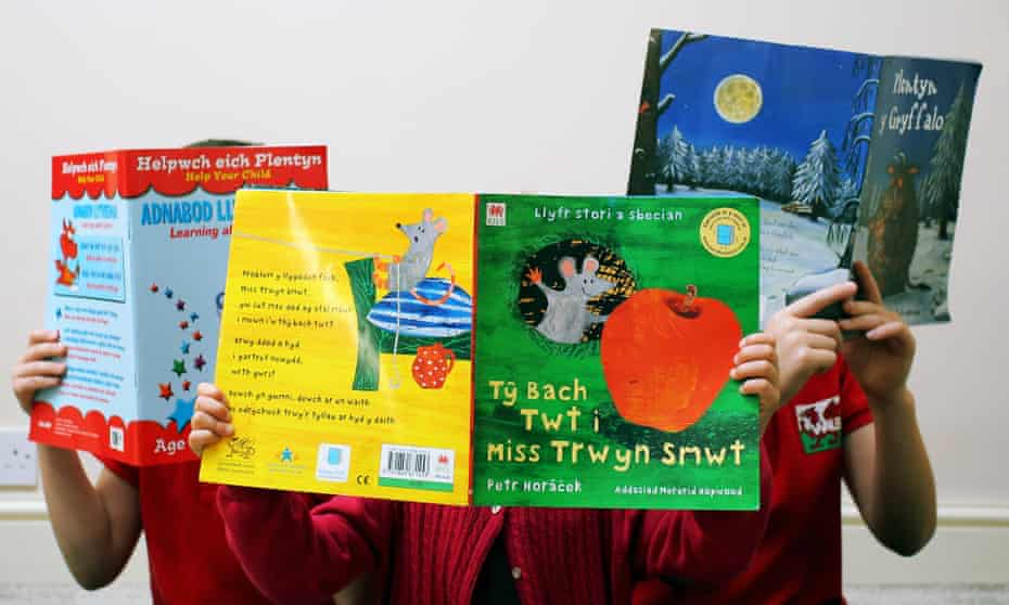 Children holding up picture books in Welsh