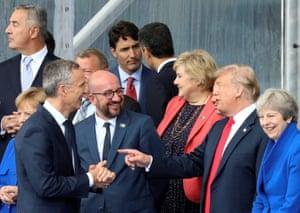 Donald Trump gestures to Jens Stoltenberg and Belgium's Charles Michel