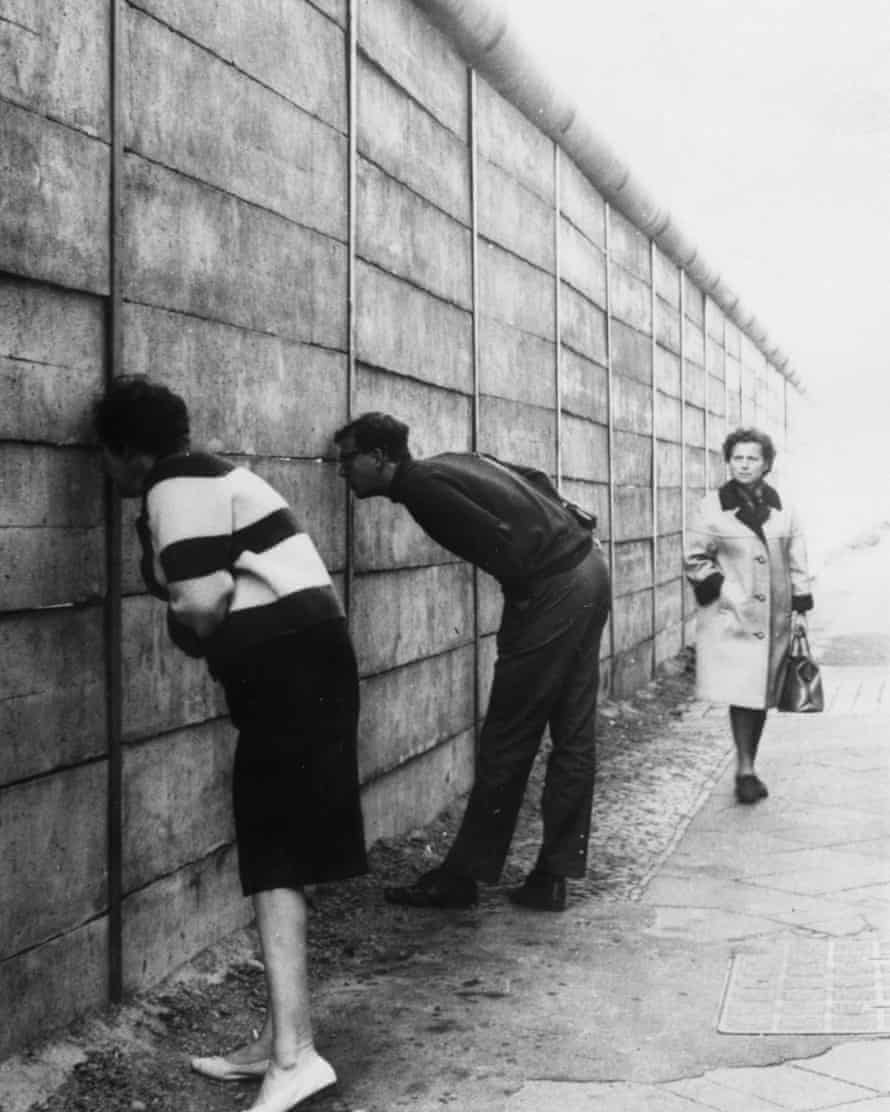 West Berliners peer through the Wall into the eastern sector near Checkpoint Charlie.