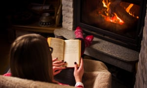Woman reading a book by the fireplace