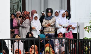 Acehnese women watch the flogging of ten people for violating Sharia law in Banda Aceh.