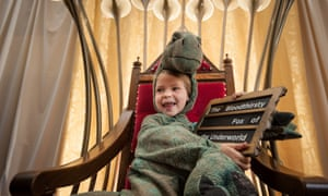 A child sits in a storytelling chair wearing a dinosaur costume, Story Museum, Oxford