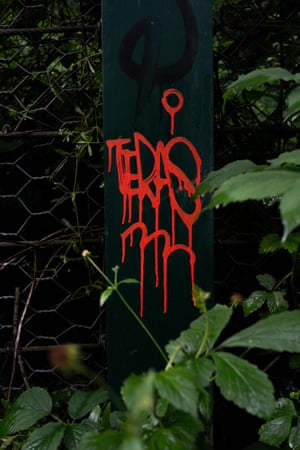 Graffiti covers a metal post to protect pedestrians against rock falls beside the Water of Leith near Stockbridge.