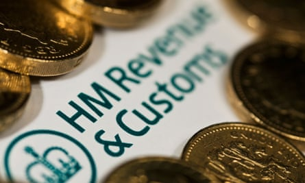 an HMRC self-assessment form surrounded by £1 coins