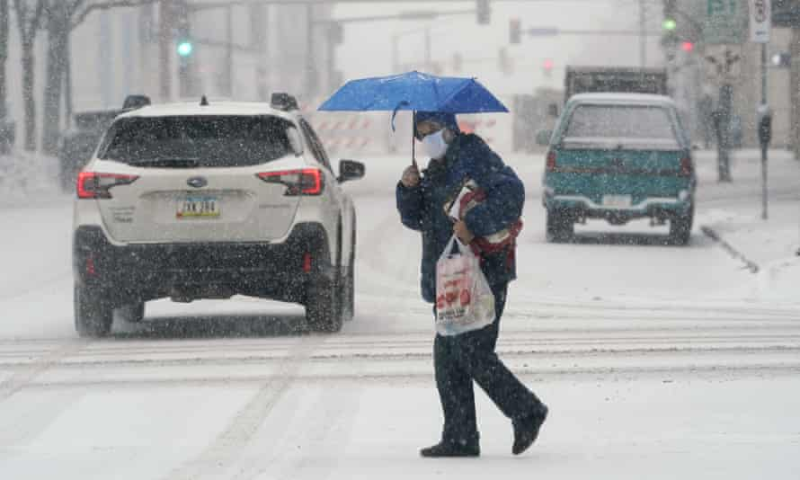 A pedestrian crosses a snow-covered street in Des Moines, Iowa, on 25 January.