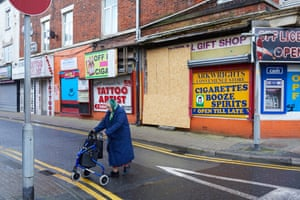 An elderly woman pushes her shopping trolley past boarded-up shops in the Fylde coast seaside resort, Blackpool