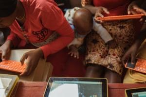 Nuru Green's daughter, Julieth, helping her mum with her classwork, in Mbeya, Tanzania