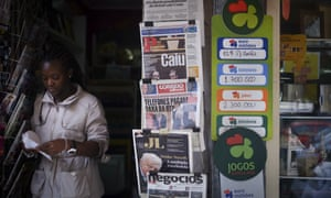 A woman leaves a kiosk displaying Portuguese newspaper front pages about the fall of the 11-day-old government.