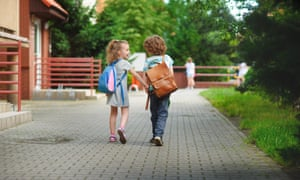 Boy and girl go to school having joined hands