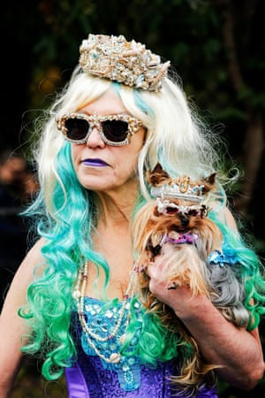 Woman and her dog wear matching mermaid costumes
