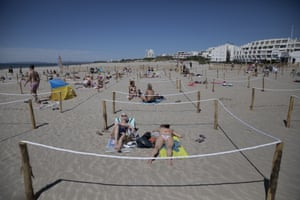 Sunbathers lie in an area marked to enforce social distancing measures in La Grande Motte, southern France.