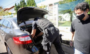 Federal police agents leave the house of Allan dos Santos, during a fake news investigation, in Brasíia on Wednesday.