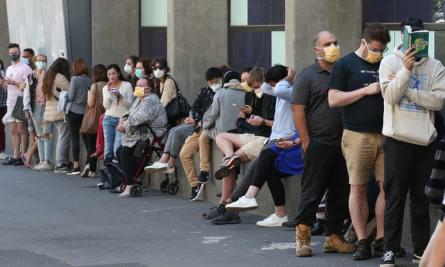 A queue of people wait for testing outside Royal Melbourne Hospital