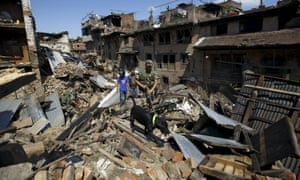 Nepalese army personnel and a sniffer dog search for victims amidst the rubble of collapsed houses in Bhaktapur, Nepal.