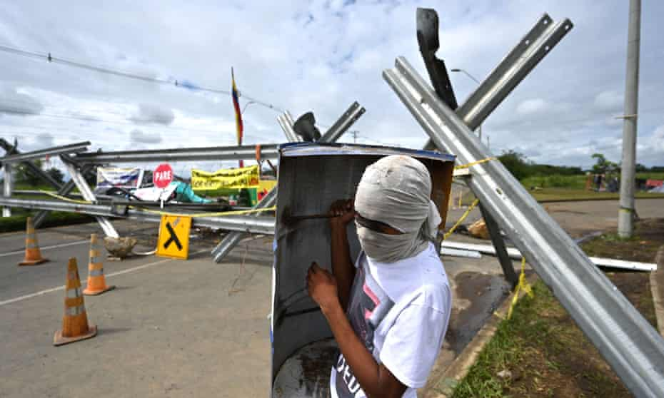 CA demonstrator holds a makeshift shield near a barricade blocking the Panamerican highway in Cali, Colombia, on Monday.