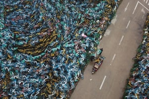 A fresh addition is delivered to a pile of bicycles from a bike-sharing service in Hefei, China