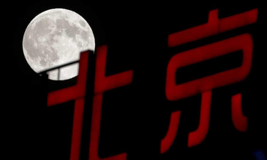 A super moon rises over Chinese calligraphy spelling out Beijing