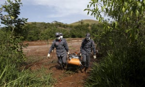 Firefighters carry a dead body by the banks of Rio Doce (Doce River)